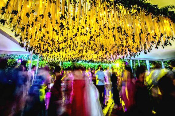Gente bailando en una fiesta con un techo decorado con lirios