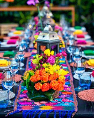 Montaje de mesa mexicana decorada con flores y colores típicos mexicanos